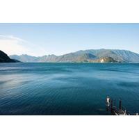 Homem Pescaria A Partir De Doca Em Borda De Lago Como